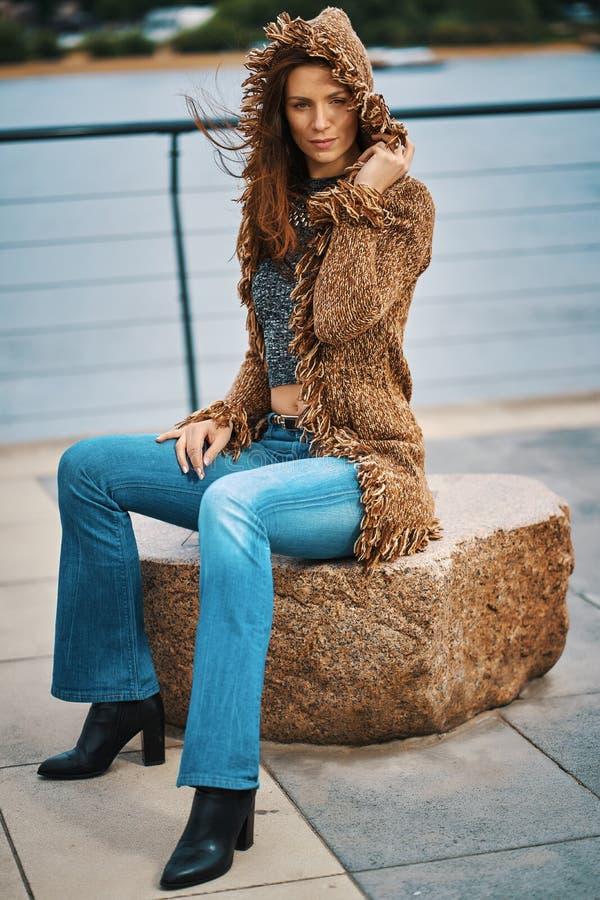 Piękna młoda kobieta pozuje na kamiennej ławce na deptaku przy rzeką obrazy stock