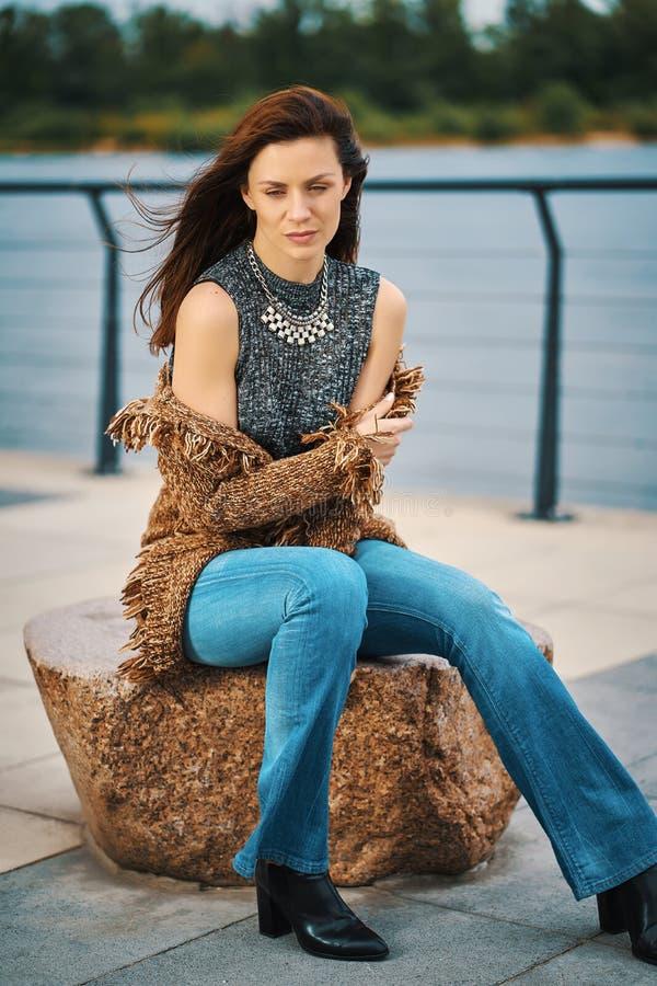 Piękna młoda kobieta pozuje na kamiennej ławce na deptaku przy rzeką zdjęcie stock