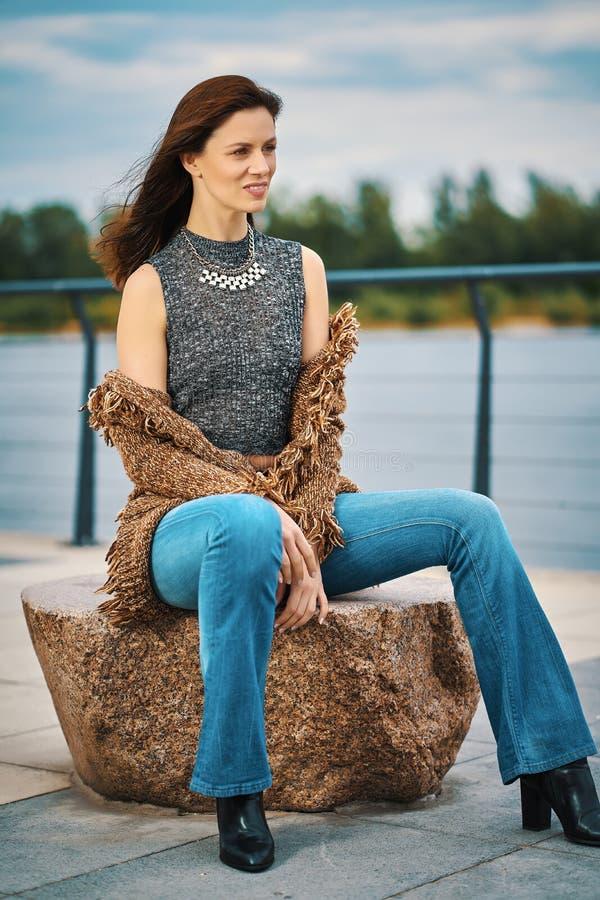 Piękna młoda kobieta pozuje na kamiennej ławce na deptaku przy rzeką obraz royalty free