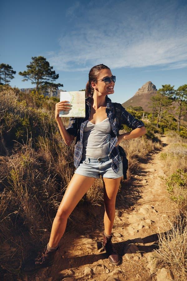 Piękna młoda kobieta pozuje z mapą outdoors zdjęcie royalty free