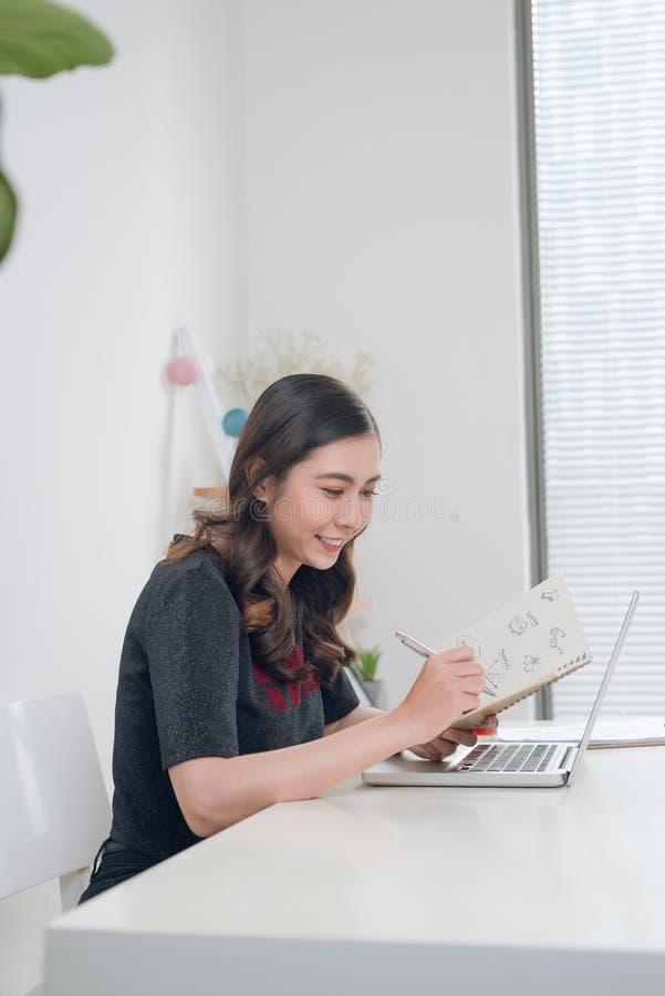 Piękna młoda kobieta pracuje od domu - writing pomysły w n zdjęcie royalty free