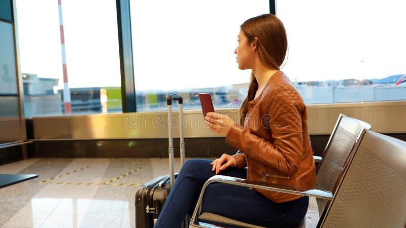 Piękna młoda kobieta przyglądająca za okno podczas gdy czekający wsiadać na samolocie z paszportem w jej ręce zdjęcie stock