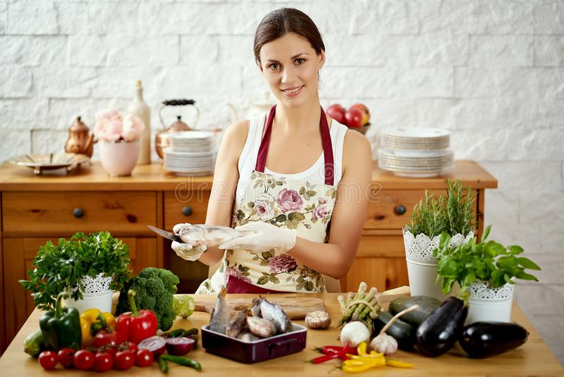 Piękna młoda kobieta przygotowywa świeżej ryby przy stołem pełno organicznie warzywa obrazy royalty free