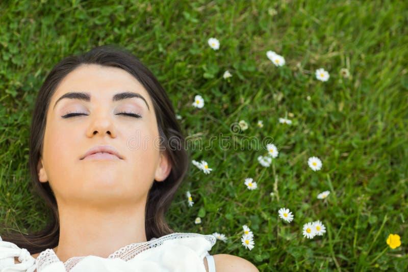 Piękna młoda kobieta relaksuje na obszarze trawiastym zdjęcia royalty free