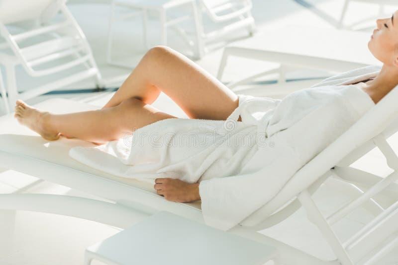 piękna młoda kobieta relaksuje na sunbed w bathrobe zdjęcia stock