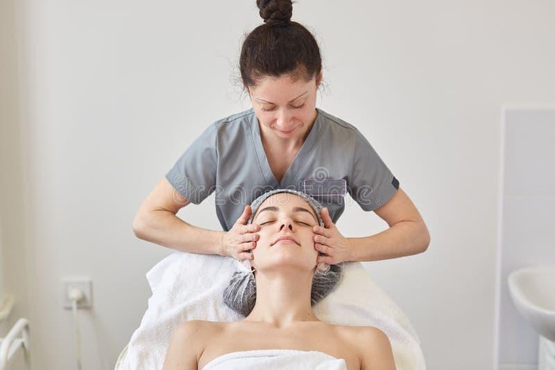 Piękna młoda kobieta relaksuje z twarz masażem przy piękno zdrojem podczas gdy kłamający na wygodnym couh, messeur w szarym medyc obraz royalty free