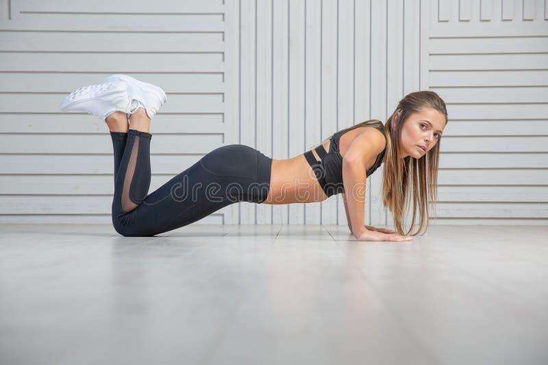 Piękna młoda kobieta robi ćwiczeniom na podłodze umacniać jej mięśnie, pracowniany portret zdjęcie royalty free