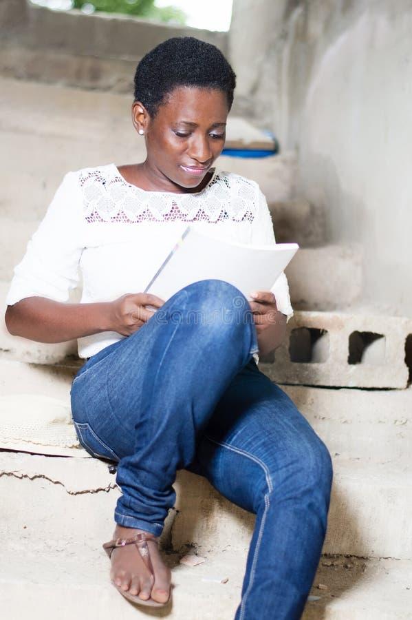 Piękna młoda kobieta robi czytaniu fotografia stock