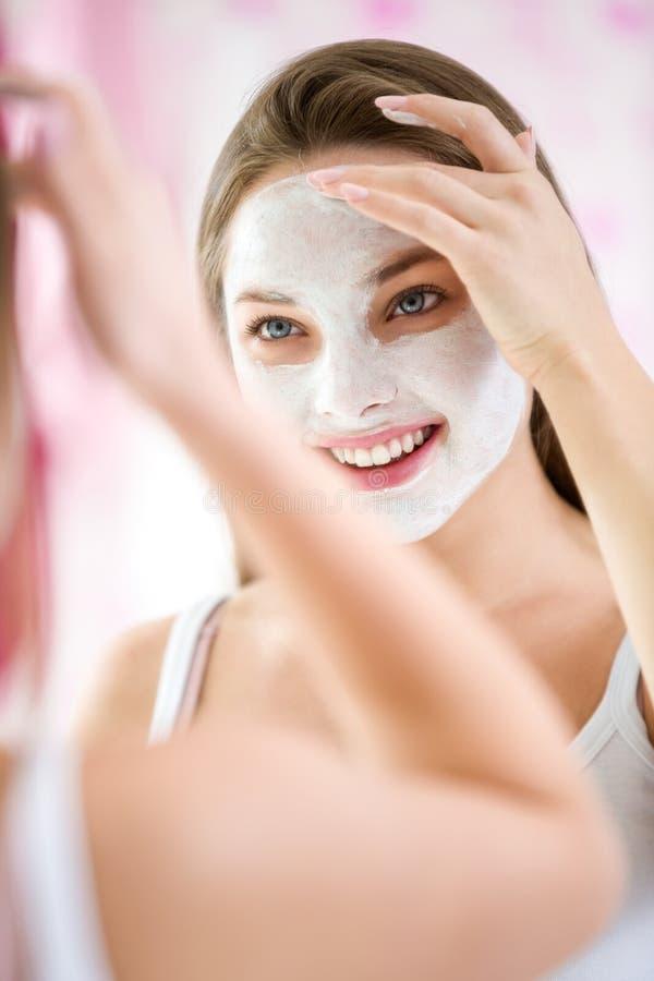 Piękna młoda kobieta robi kosmetyk masce na jej twarzy zdjęcie stock