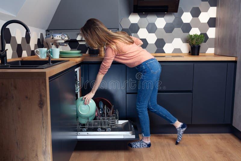 Piękna młoda kobieta robi naczyniom w kuchni obraz stock