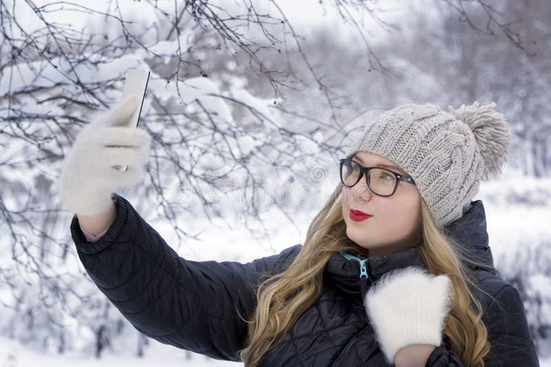 Piękna młoda kobieta robi selfie w zima parku plus rozmiaru model na śnieżnym tle, zdjęcie stock