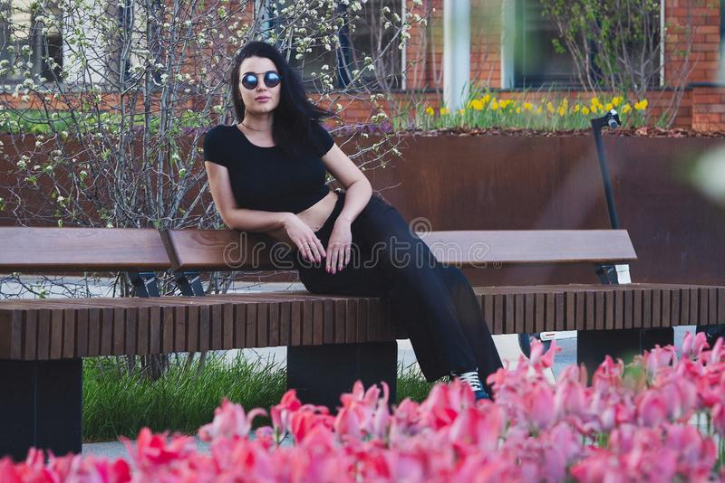 """PiÄ™kna mÅ'oda kobieta siedzÄ…ca we współczesnym parku w pobliżu kwiatów kwiatów o zachodzie sÅ'oÅ""""ca zdjęcie stock"""