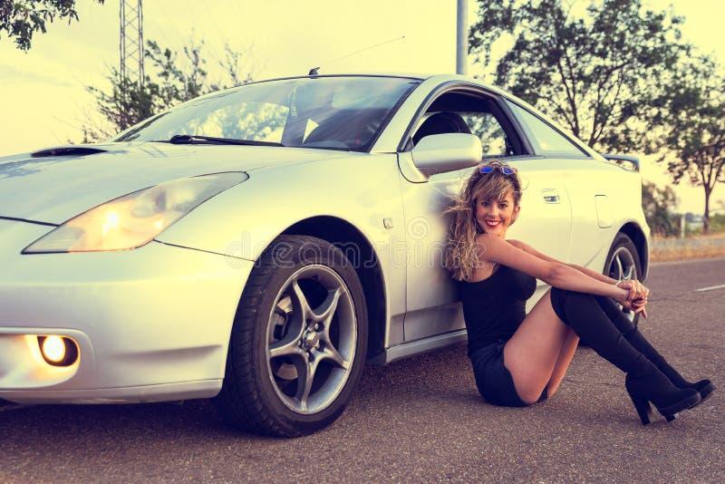 Piękna młoda kobieta siedzi na stronie sportowego samochód w skrótach zdjęcia stock