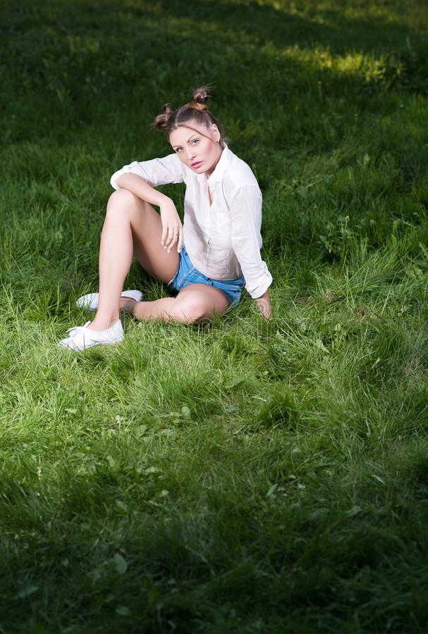 Piękna młoda kobieta siedzi na trawie w modnych przypadkowych ubraniach obraz stock