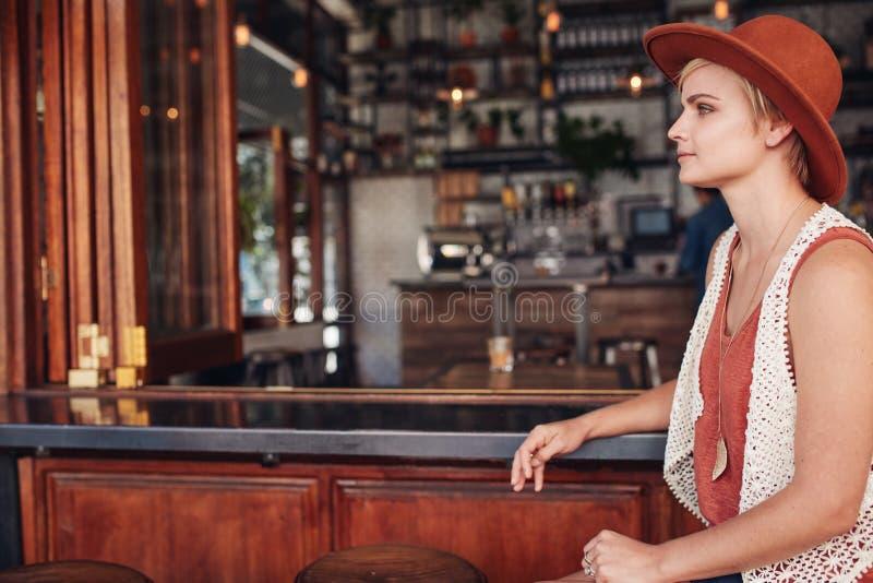 Piękna młoda kobieta siedzi samotnie przy baru kontuarem obrazy stock