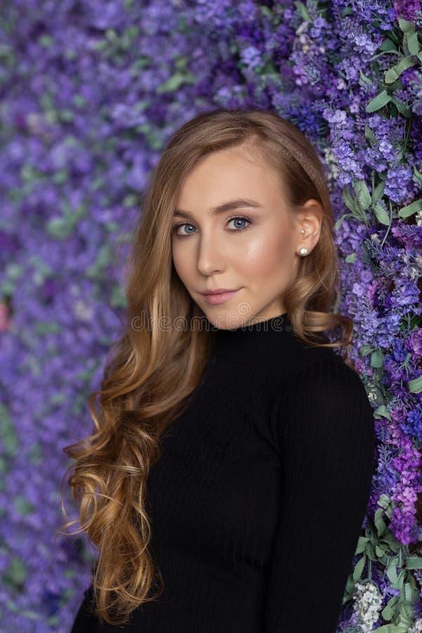 Piękna młoda kobieta stoi blisko kwiat ściany salowy Lookin obraz royalty free