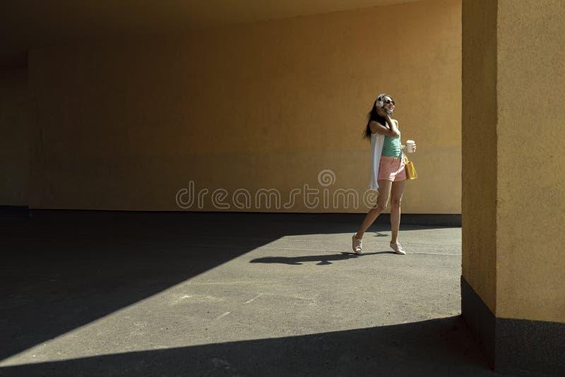 Piękna młoda kobieta stoi przeciw kolor żółty ścianie w hełmofonach obrazy stock
