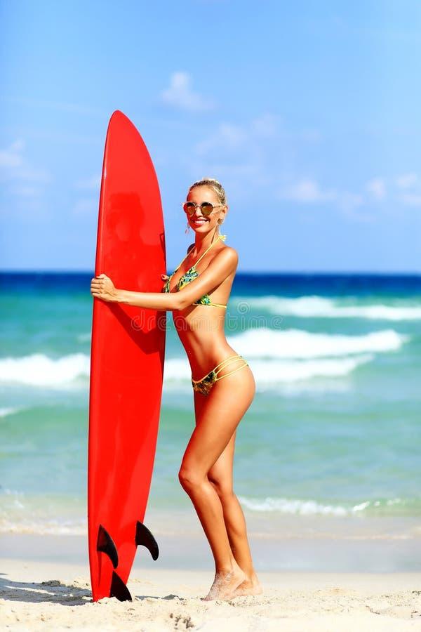 Piękna młoda kobieta surfingowa dziewczyna w bikini z czerwonym surfboard a zdjęcia stock