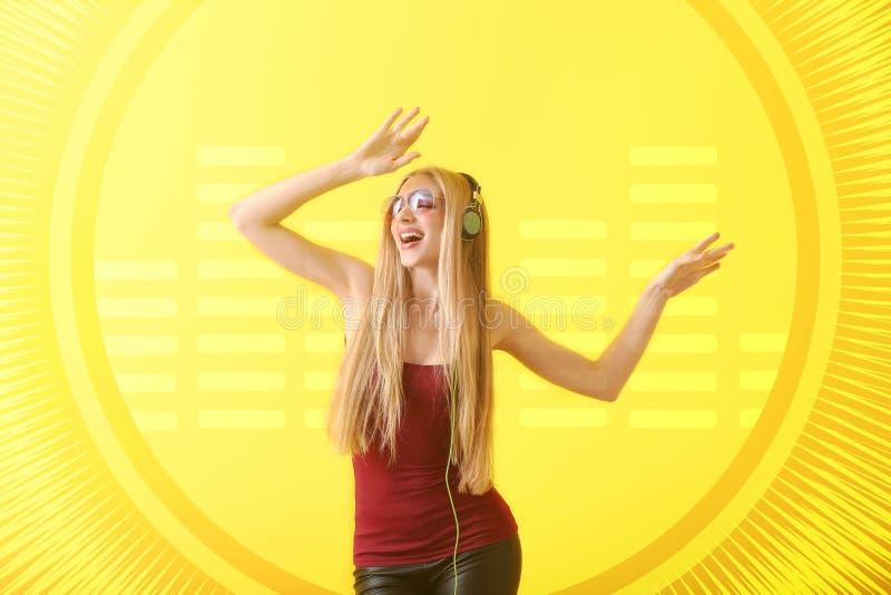 Piękna młoda kobieta tanczy przeciw koloru tłu z hełmofonami obraz stock