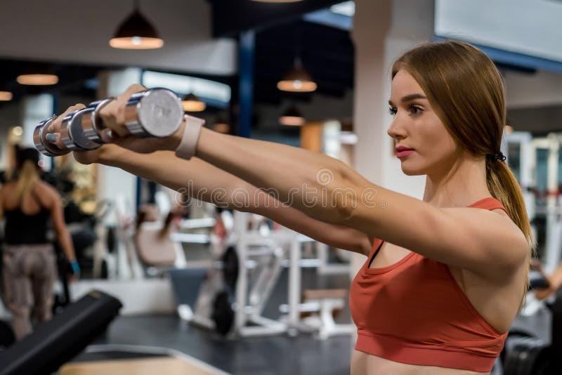 Piękna młoda kobieta trenuje deltoid w gym fotografia royalty free