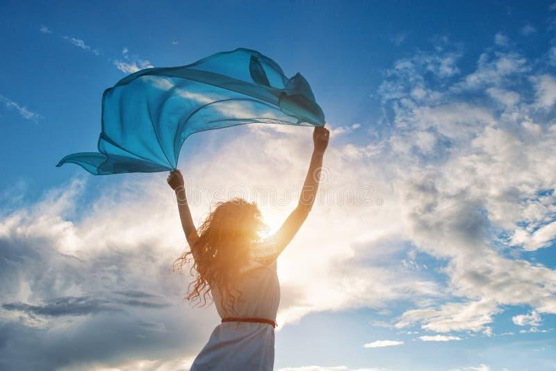Piękna młoda kobieta trzyma błękitnego szalika na wiatrze obraz stock