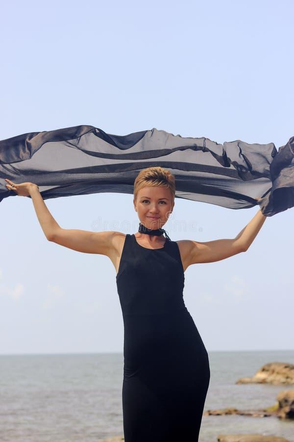 Piękna młoda kobieta trzyma czarną tkaninę przy wiatrem przy nadmorski w czarnej wieczór sukni obrazy stock