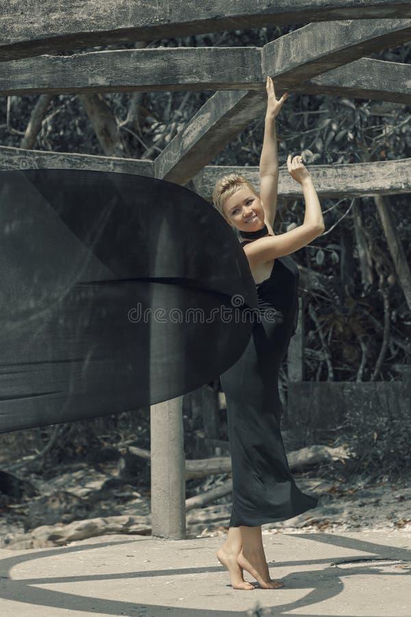 Piękna młoda kobieta trzyma czarną tkaninę przy wiatrem w czarnej wieczór sukni obraz royalty free