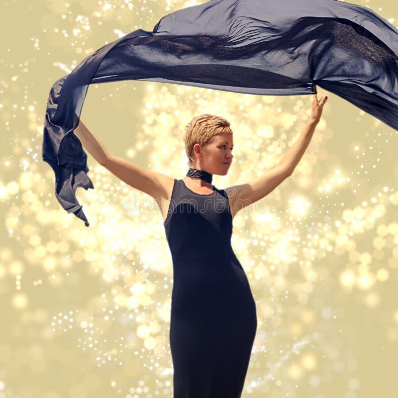 Piękna młoda kobieta trzyma czarną tkaninę przy wiatrem w czarnej wieczór sukni obrazy royalty free