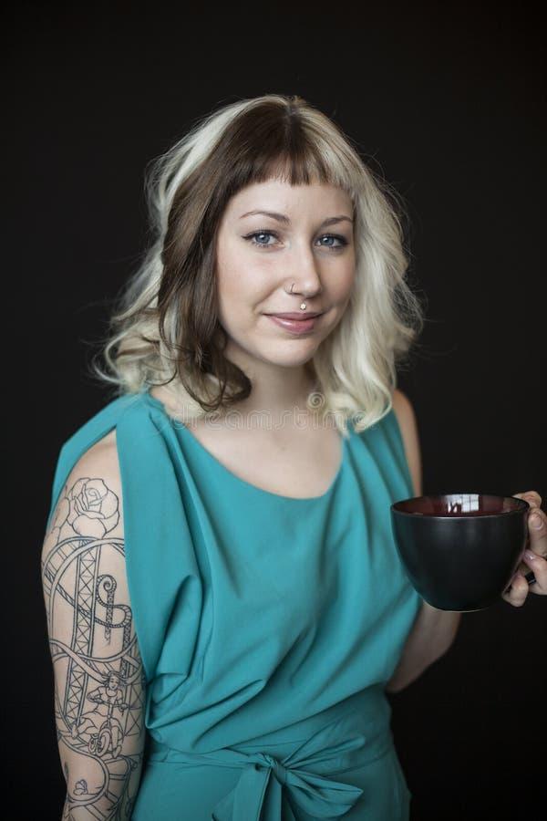 Piękna młoda kobieta Trzyma Czarnego Cof z Brown oczami i włosy zdjęcie stock