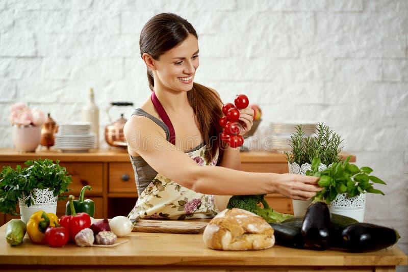 Piękna młoda kobieta trzyma pomidory w kuchni przy stołem organicznie warzywa pełno obraz stock