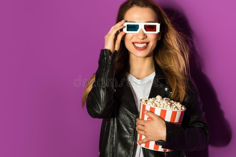 piękna młoda kobieta trzyma pudełko popkorn i ono uśmiecha się przy kamerą w 3d szkłach obraz royalty free