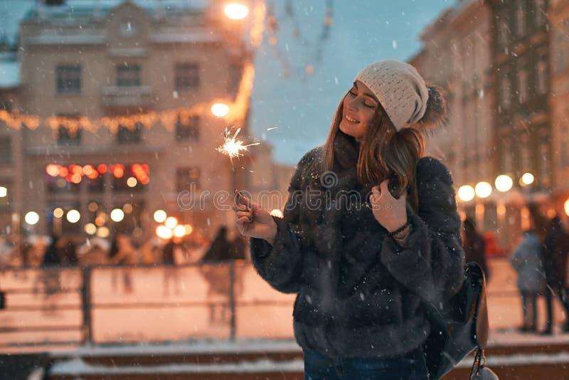 Piękna młoda kobieta trzyma sparkler w futerkowym żakiecie cieszy się zima Bożenarodzeniowego nastrój w starym śnieżnym Europejsk zdjęcia stock