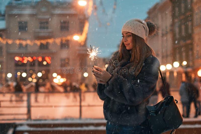 Piękna młoda kobieta trzyma sparkler w futerkowym żakiecie cieszy się zima Bożenarodzeniowego nastrój w starym śnieżnym Europejsk zdjęcie royalty free
