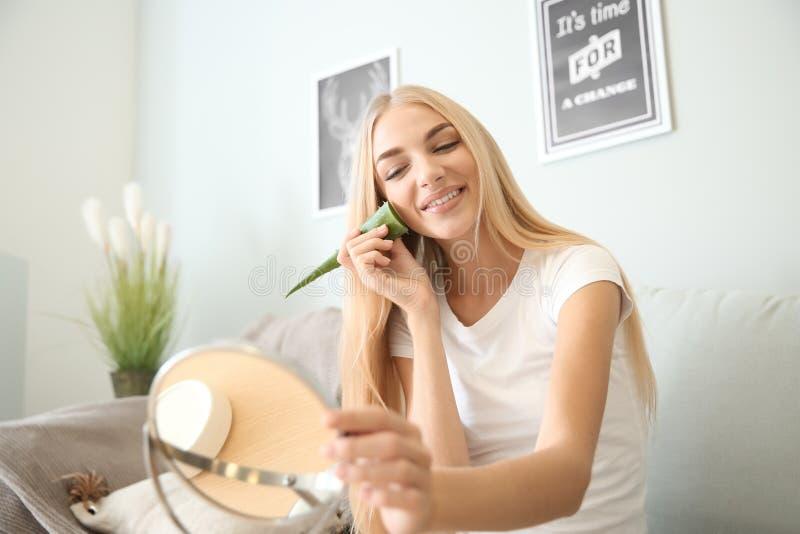 Piękna młoda kobieta używa aloesu Vera w domu obrazy royalty free