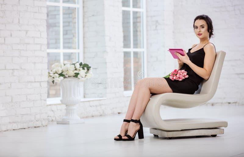 Piękna młoda kobieta używa pastylkę podczas gdy siedzący na galanteryjnym krześle fotografia royalty free