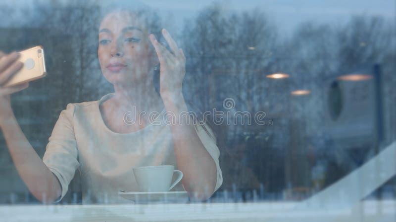 Piękna młoda kobieta używa telefon sprawdzać ona uzupełniał selfie i bierze obraz royalty free