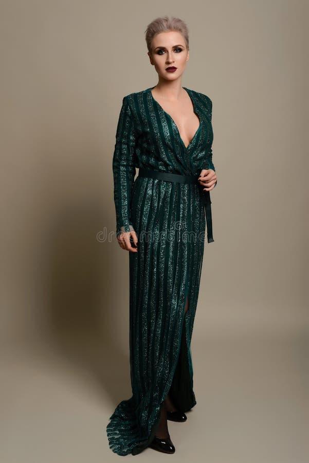 Piękna młoda kobieta ubierał w eleganckiej turkusowego błękita przewiązki maksiej sukni pozuje na tle zdjęcia royalty free