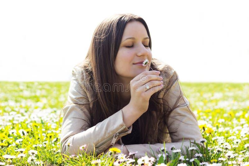 Piękna młoda kobieta wącha kwiaty fotografia stock