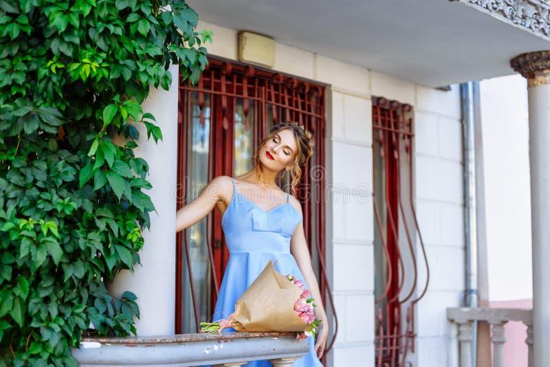 Piękna młoda kobieta w błękitnym smokingowym pozuje outside blisko kolumny obrazy royalty free