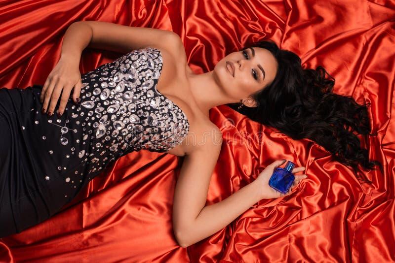 Piękna młoda kobieta w błyszczącej sukni z butelką pachnidło kłama na czerwonym atłasie zdjęcia stock