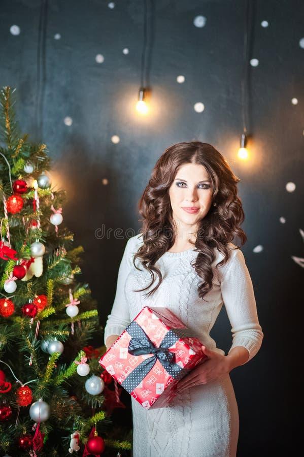 Piękna młoda kobieta w białej pulower sukni trzyma pudełko z prezentem przed choinką Brunetka w bedroo zdjęcie stock