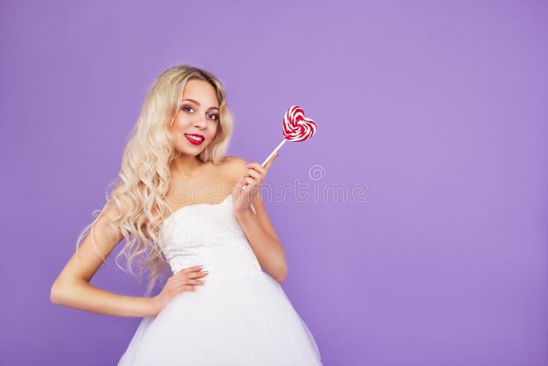 Piękna młoda kobieta w biel sukni z lizakiem Atrakcyjna dziewczyna na purpurowym tle trzyma serce kosmos kopii obrazy stock