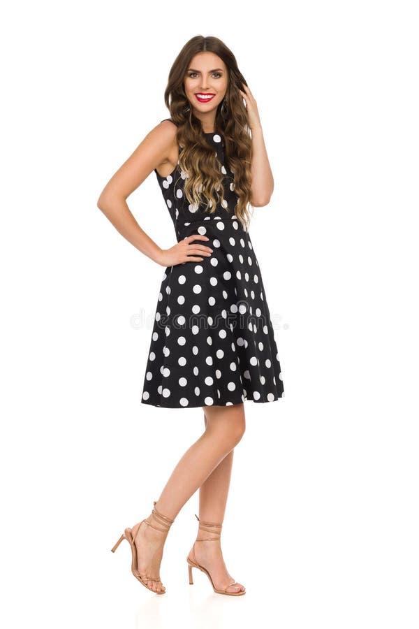 Piękna młoda kobieta W Czarnej koktajl sukni W polek kropkach I Beżowych szpilki sandałach Stoi zdjęcie stock