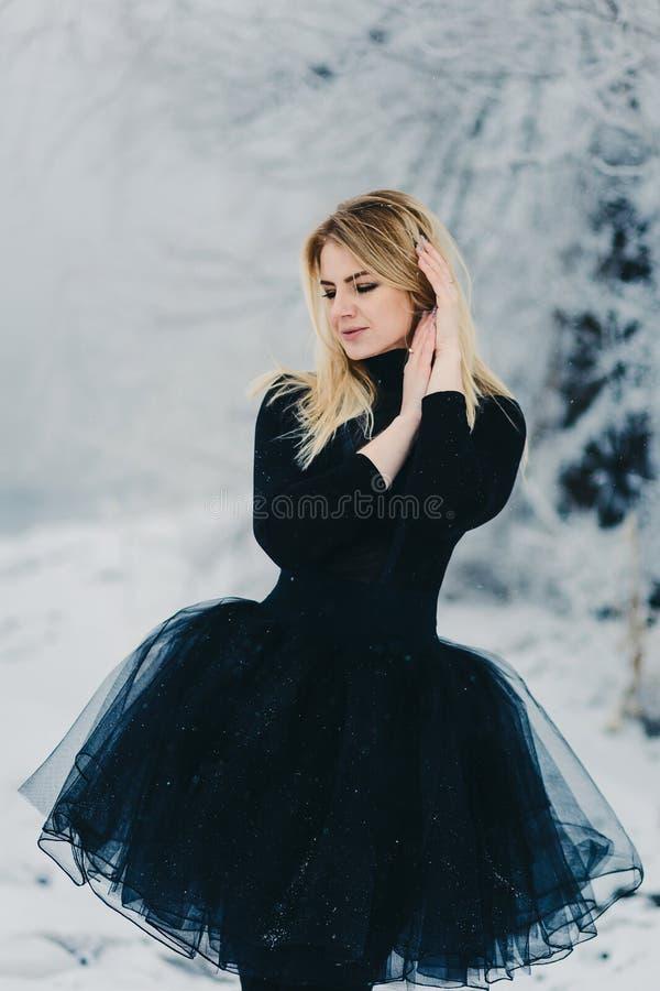 Piękna młoda kobieta w czarnej sukni w zima lesie obrazy royalty free