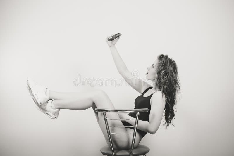 Piękna młoda kobieta w czarnym kombinezonu obsiadaniu zdjęcie royalty free