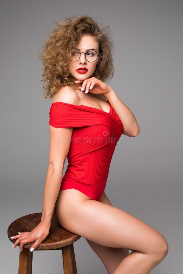Piękna młoda kobieta w czerwonej ciało bieliźnie pozuje podczas gdy siedzący na krześle na popielatym tle zdjęcia royalty free
