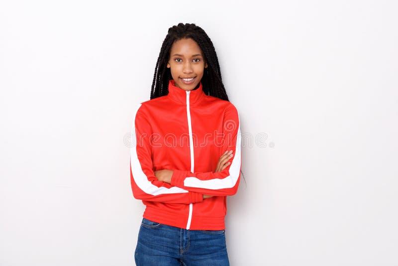 Piękna młoda kobieta w czerwonej kurtki pozyci z rękami krzyżował na białym tle zdjęcie royalty free