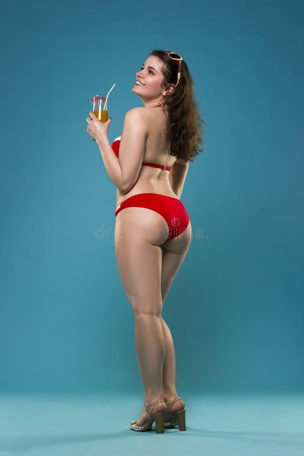 Piękna młoda kobieta w czerwonym bikini z koktajlem na błękitnym tle obrazy royalty free