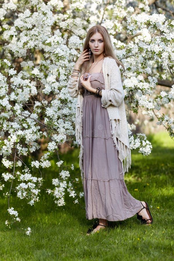 Piękna młoda kobieta w długim smokingowym boho stylu na zielonej trawy un zdjęcie stock