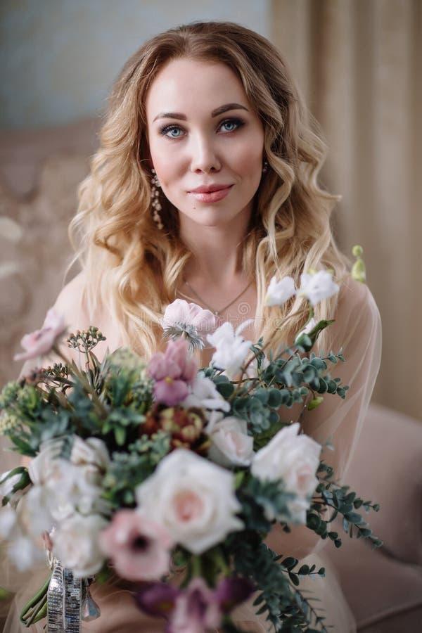 Piękna młoda kobieta w domowej sukni w boudoir, dekorującym z pięknymi kwiatami, siedzi na białym łóżku z baldachimem, fas obrazy stock